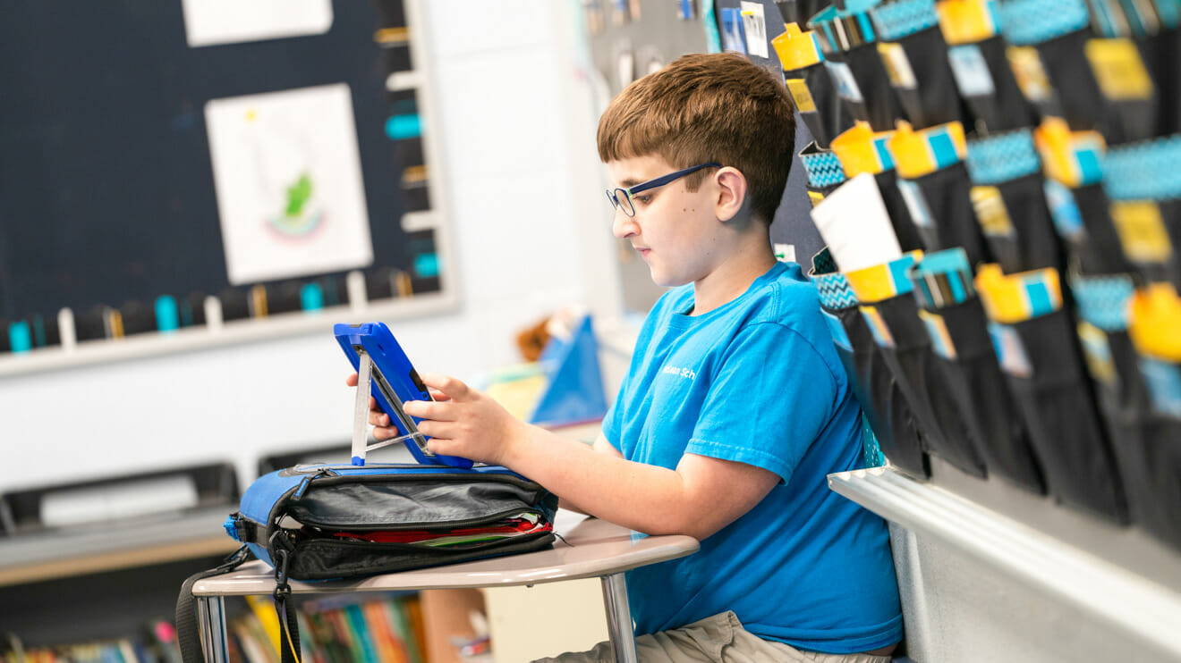 Boy sits in classroom on tablet