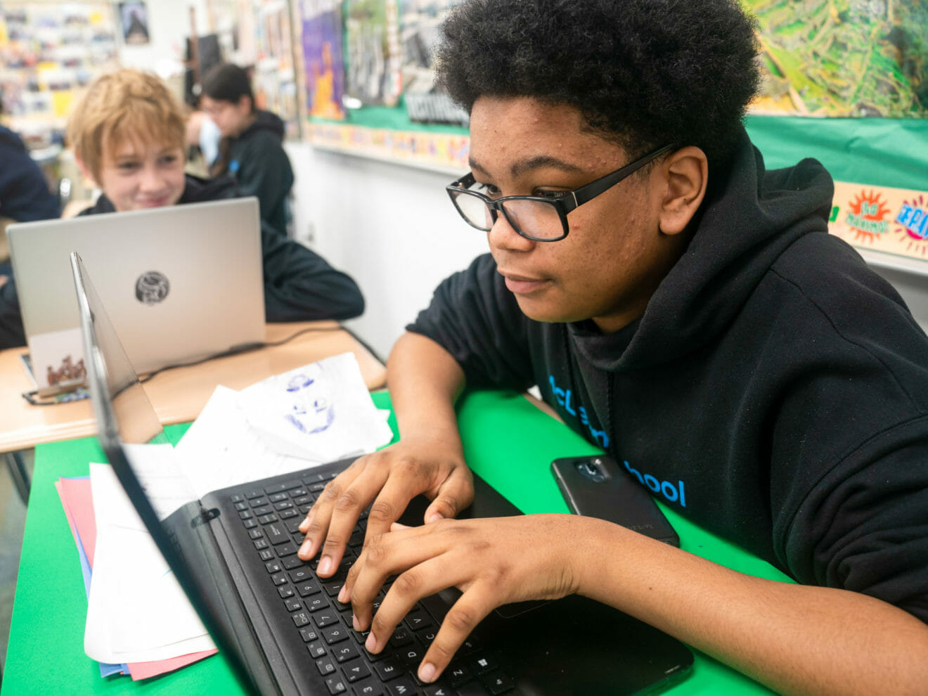 Boy in glasses uses laptop in class