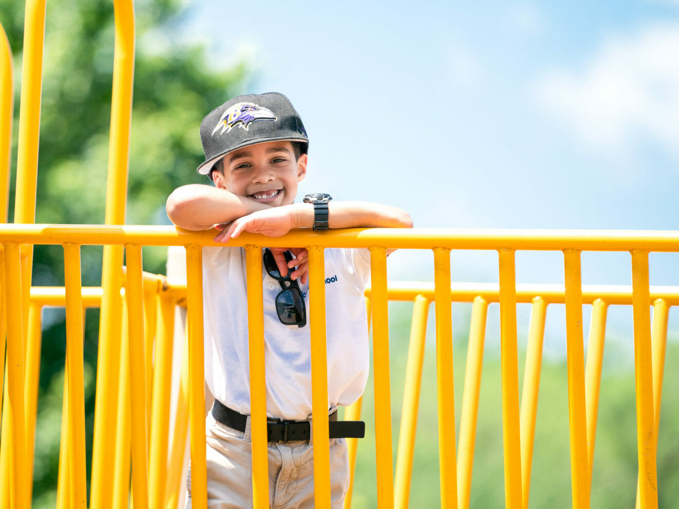 Smiling boy stands on bridge of playground
