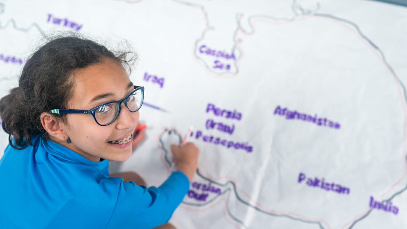 Smiling girl looks up from drawing large map of Persia