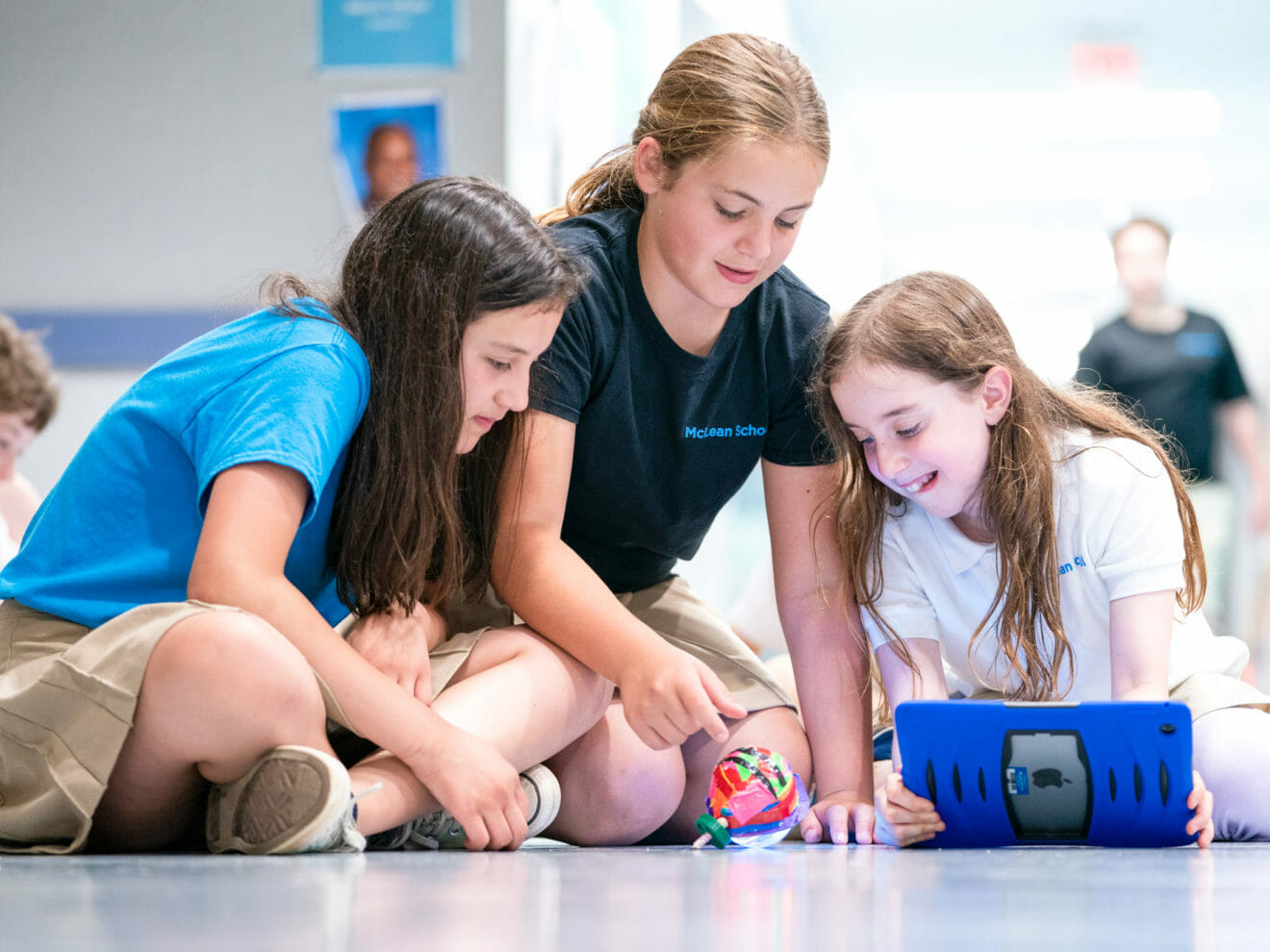 Three girls work on project in school hall