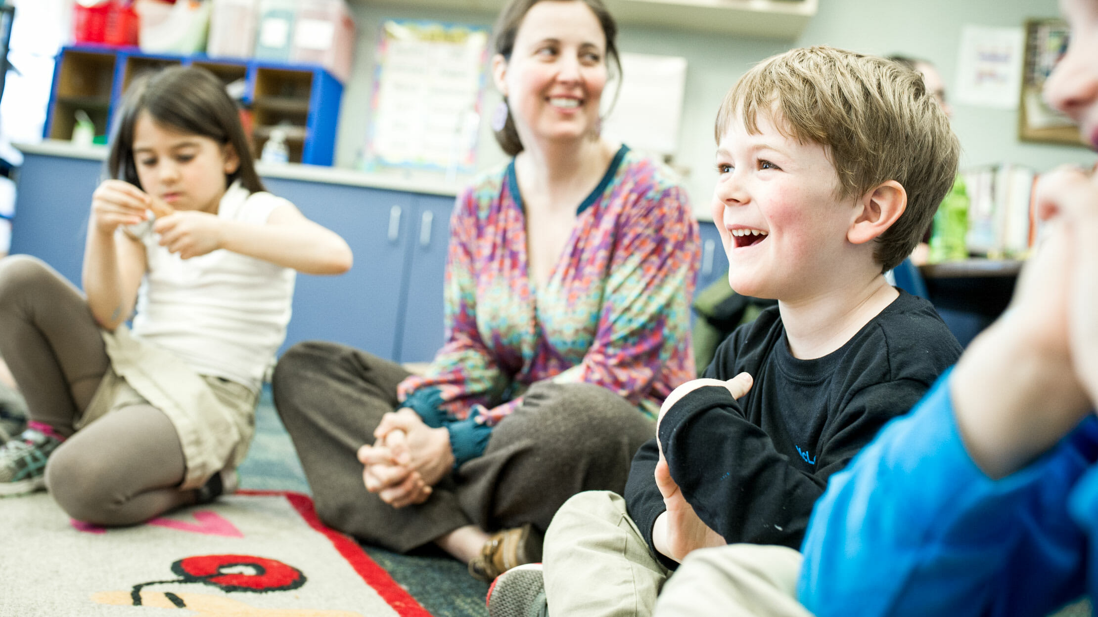 Laughing boy sits on classroom floor