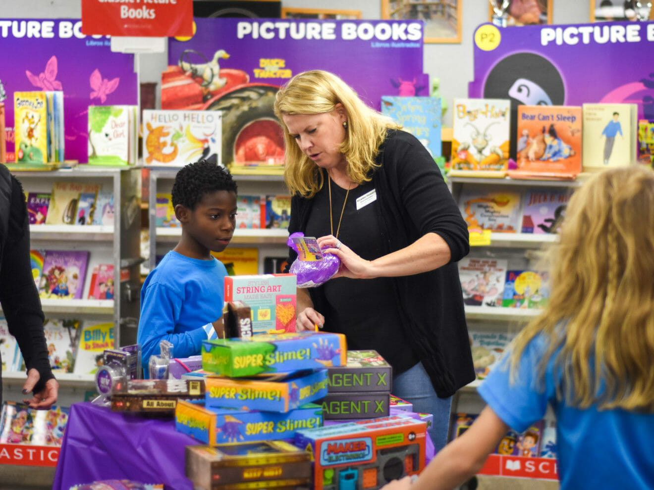 Volunteering parent helps student at book fair