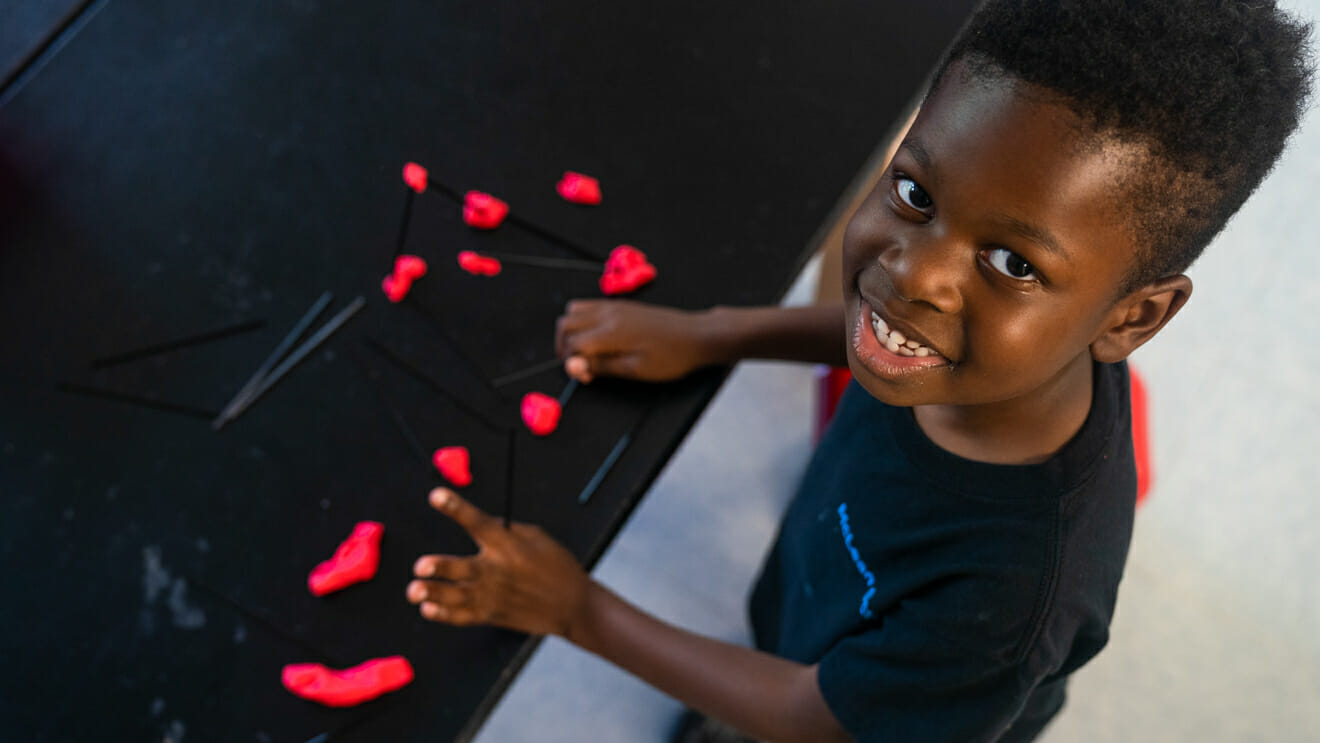 Smiling boy looks up from model putty and sticks