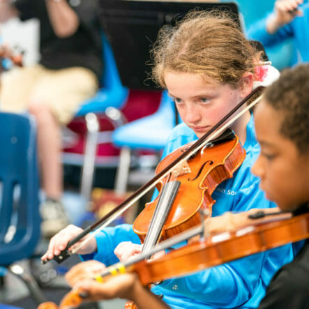Students play violins in orchestra