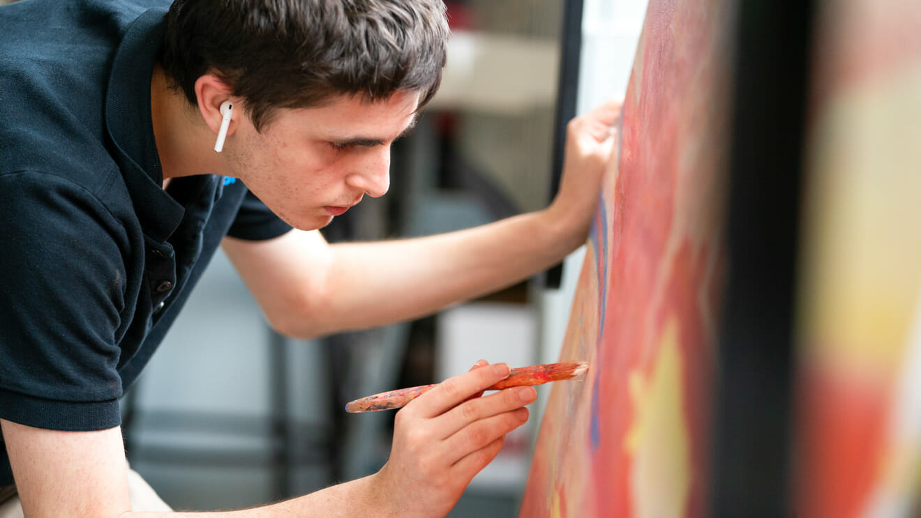 Upper school student leans over large painting