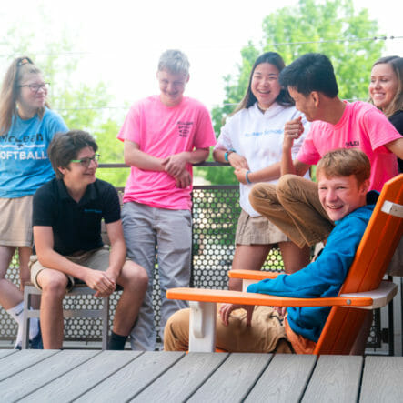 Upper school students laugh together on porch