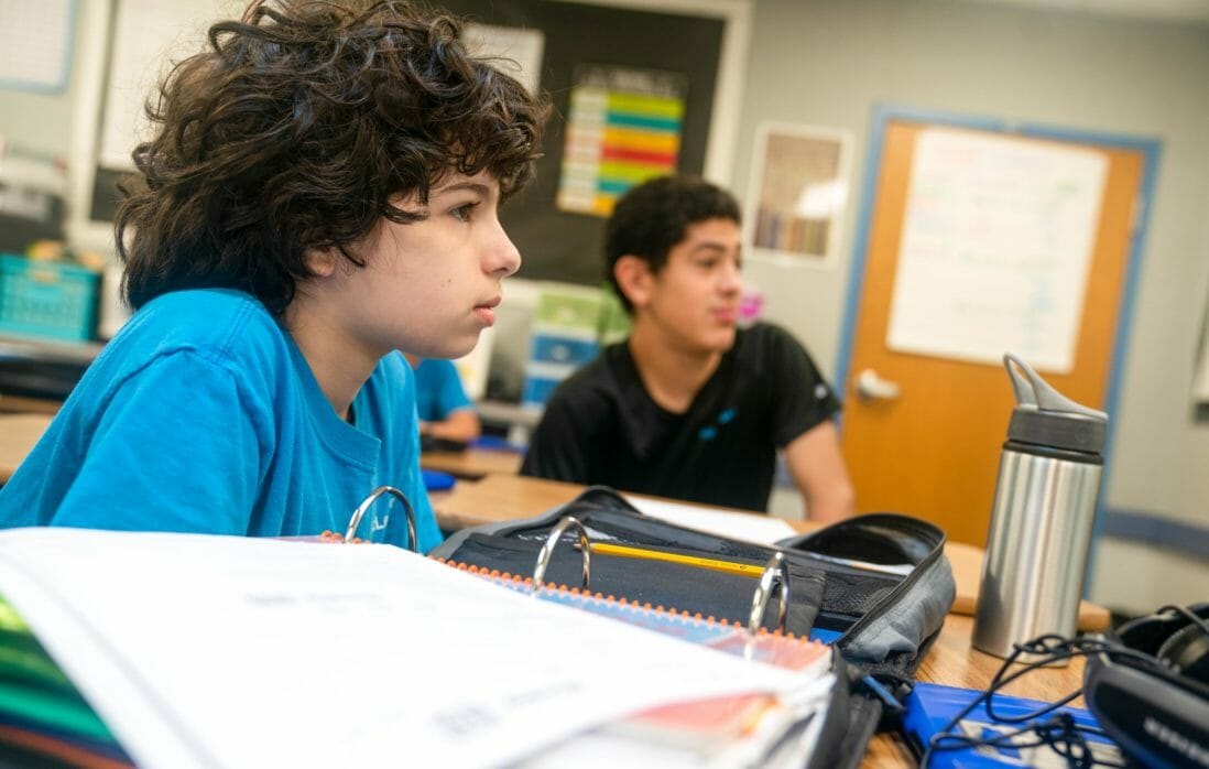 Young boy with curly hair sits in front of binder