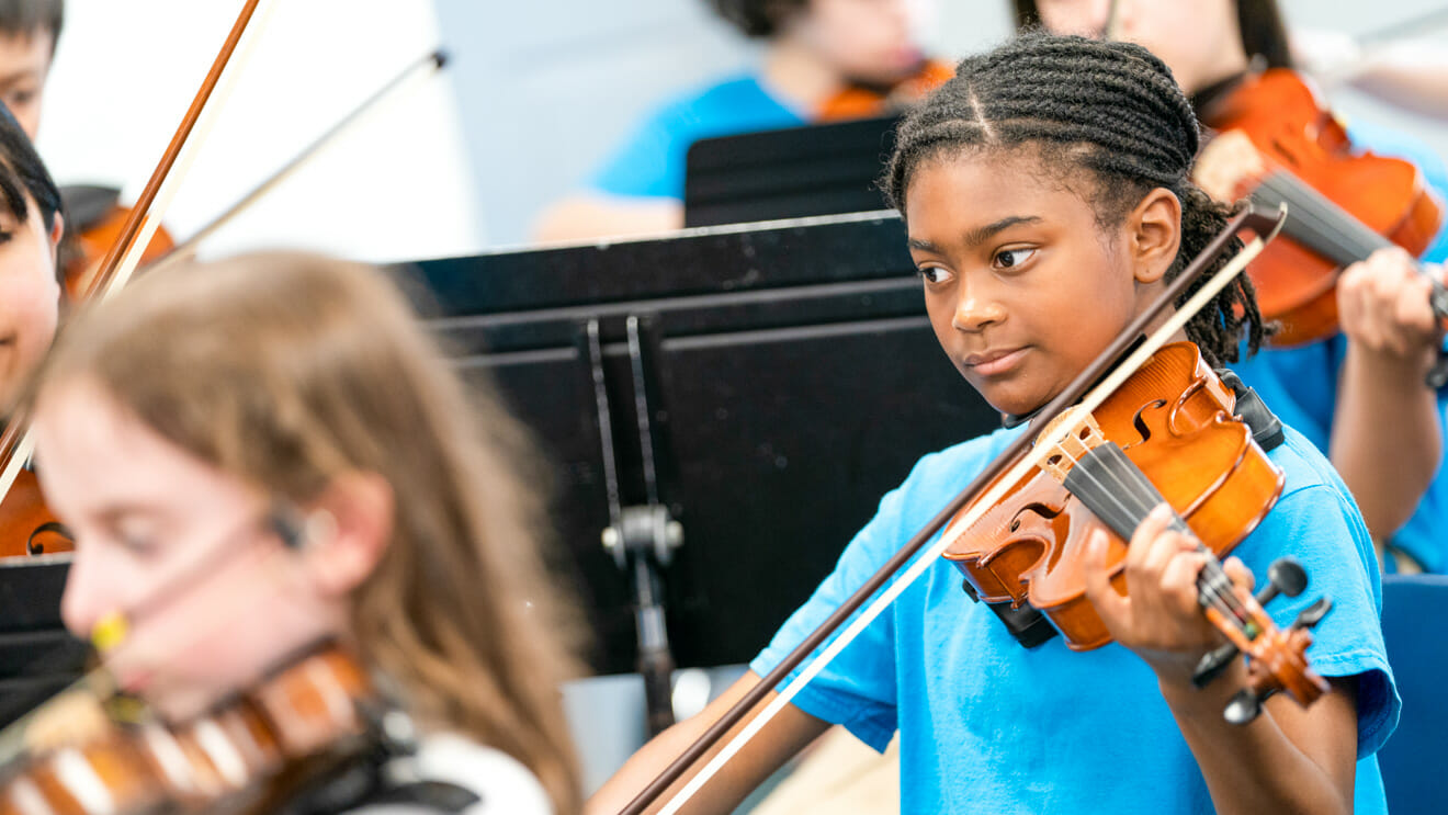 Young girl plays violin in orchestra