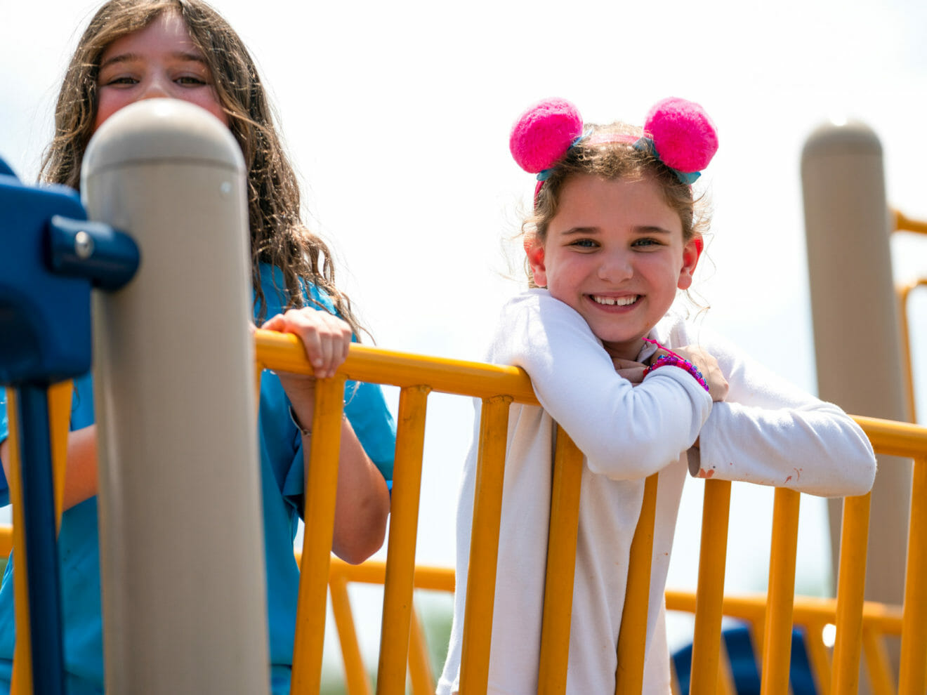 Smiling young girls stand on playground bridge