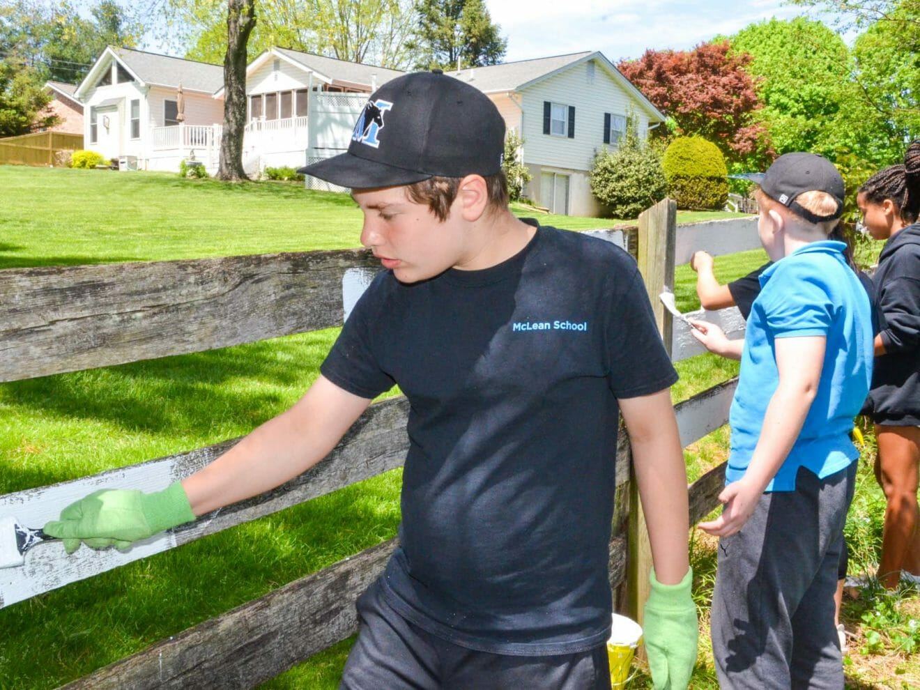 Middle school students paint fence for community service