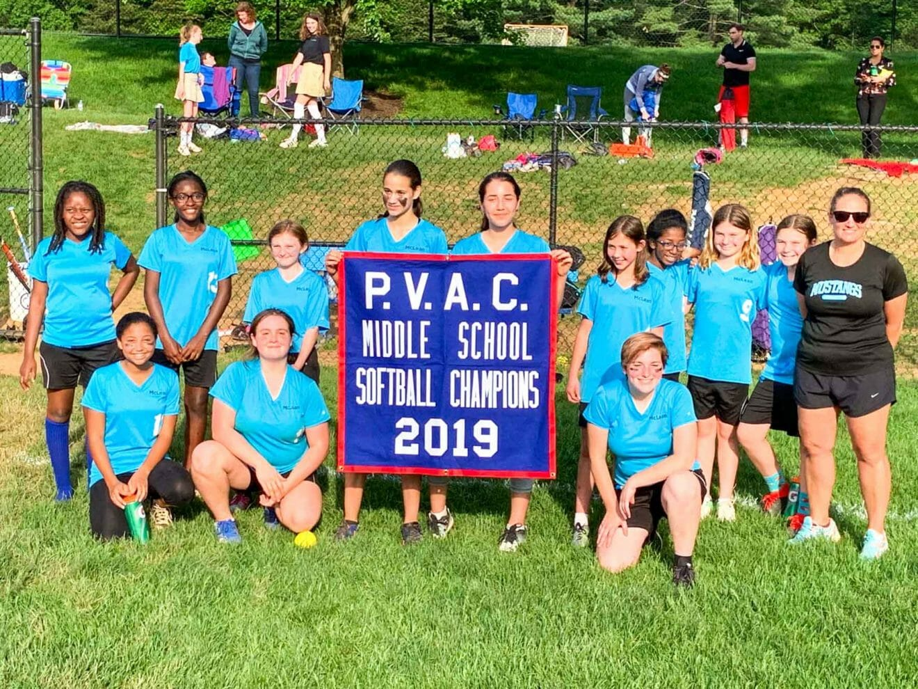 Middle school softball team poses with PVAC Championship banner