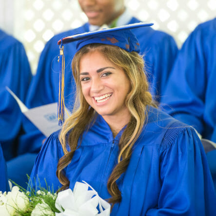 Smiling girl sits in row at graduation