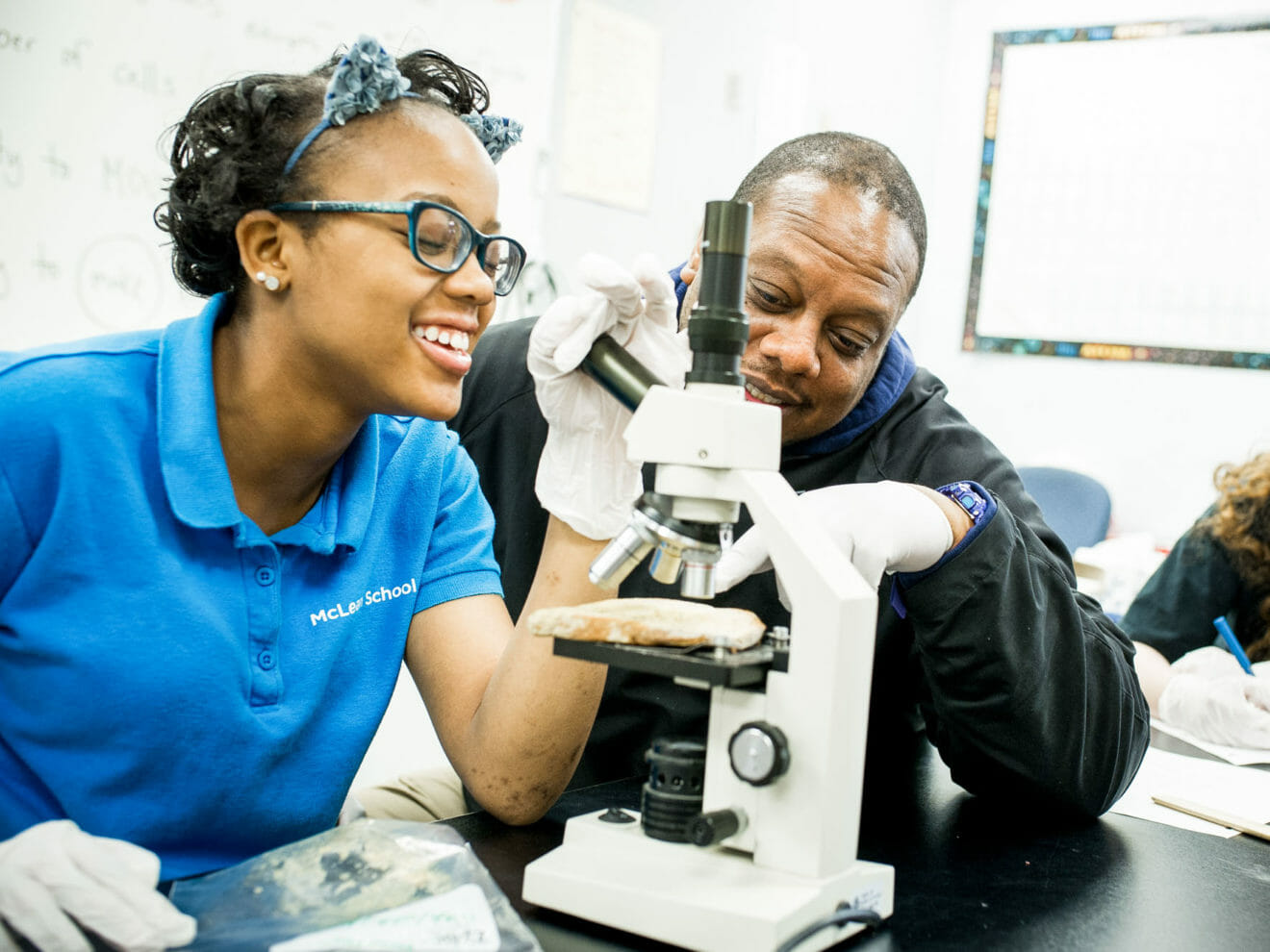 Teacher helps student with microscope